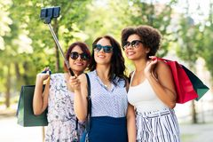 Women with shopping bags taking selfie outdoors. Sale, friendship and technology concept - happy young women with shopping bags taking selfie by smartphone in royalty free stock photo