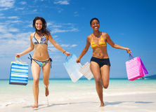 Women with shopping bags on a tropical beach Royalty Free Stock Image