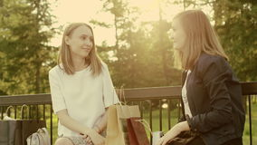 Women with shopping bags. Two women look in the shopping bags and talking about their purchases in the park stock footage