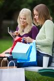 Women With Shopping Bags Using Tablet PC Outdoors Royalty Free Stock Photo