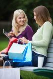 Women With Shopping Bags Using Tablet PC Outdoors Royalty Free Stock Images