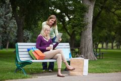 Women With Shopping Bags Using Tablet PC At Park Royalty Free Stock Images