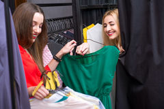 Women shopping clothes. Happy women choosing garments near the wardrobe at the clothing store. Female friends having fun shopping clothes stock images