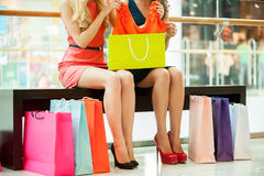 Women shopping. Cropped image of two young women sitting in shopping mall with bags Royalty Free Stock Image