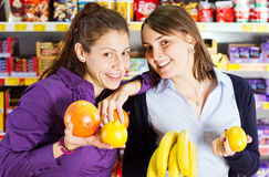 Women shopping in grocery store. Two smiling young women shopping in a grocery store holding fruits stock photos