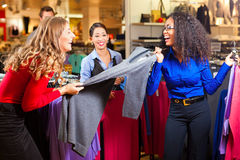 Women in a shopping mall with clothes. Three women in a shopping mall downtown looking for clothes Stock Image