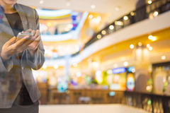 Women in shopping mall using mobile phone. Royalty Free Stock Image