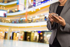 Women in shopping mall using mobile phone. Stock Photo