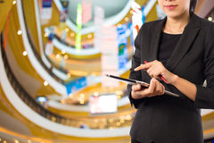 Women in shopping mall using mobile Tablet PC. Royalty Free Stock Photos