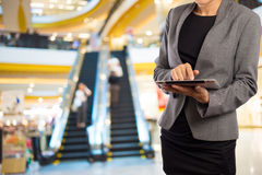 Women in shopping mall using mobile Tablet PC. Stock Images
