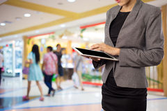 Women in shopping mall using mobile Tablet PC. Royalty Free Stock Images