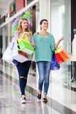 Women in the shopping mall. Young happy women with bags in the shopping mall Stock Image