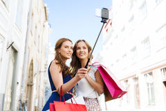 Women shopping and taking selfie by smartphone. Sale, technology, friendship and people concept - happy young women with shopping bags taking picture by stock photo