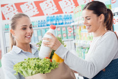 Women shopping together at the supermarket. Happy women doing grocery shopping together at the supermarket, one is putting a milk bottle in a bag Stock Image