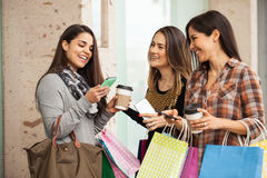 Women shopping and using their smartphones Royalty Free Stock Photography