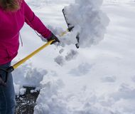 Women shoveling driveway after spring snow storm. A women is shoveling over one foot of snow wearing a pink hooded sweatshirt and black gloves after a spring stock photography