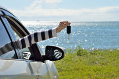 Women showing car keys out window. Sea background Stock Image