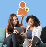 Women showing a friend request icon and using a tablet royalty free stock photos