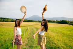 Women showing the landscape. Happy young women arms raised with hats in a green landscape Royalty Free Stock Images
