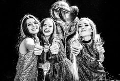 Women showing thumbs up. Black and white photo of three gorgeous women showing thumbs up and holding glasses of champagne Stock Image