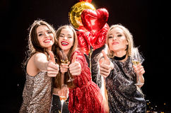 Women showing thumbs up. Three gorgeous women showing thumbs up and holding glasses of champagne Royalty Free Stock Photo