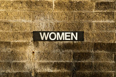Women sign on brick wall. Close up of women sign on brick wall Stock Images