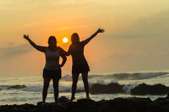 Women Silhoueted Sunrise Ocean Stock Photo