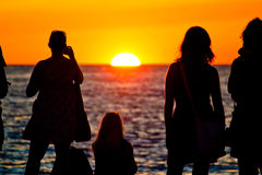 Women silhouette watching sunset on sea coast Stock Images