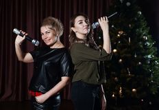 Women sing on stage in microphones in karaoke against the Christmas tree stock photos