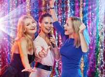 Women singing dancing at party. Happy beautiful girls having fun and singing at party Stock Photos
