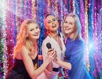 Women singing at party. Happy beautiful girls having fun and singing at party Royalty Free Stock Images