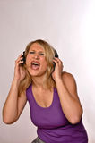 Women Singning With Headphones. Portrait Of A Beautiful Blond Woman Singing With Headphones Stock Image