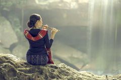 Women sit back flute at the forest with a waterfall.