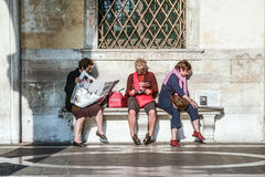 Women sit at a bench and read newspaper and books Stock Image