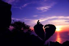 Women sit on broken heart-shaped stone on a mountain. royalty free stock photos