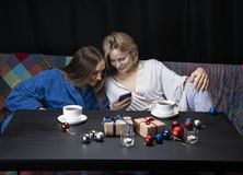 Women in home clothes drink tea. Black background. Women sit on the couch and look at the phone. New Year`s toys lie on the table in front of them, candles are stock photography