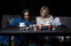 Women in home clothes drink tea. Black background. stock photography
