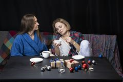 Women in home clothes drink tea. Black background. Women sit on the couch and look at the phone. New Year`s toys lie on the table in front of them, candles are stock images
