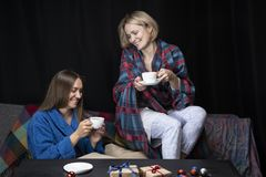 Women in home clothes drink tea. Black background. stock images
