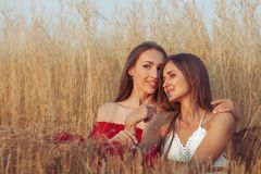 Women sit embracing each other. Stock Photos