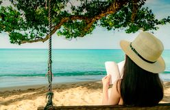 Women sit and reading a book on swings under the tree by the sea. Back view of Asian woman with straw hat relax and enjoy stock photography