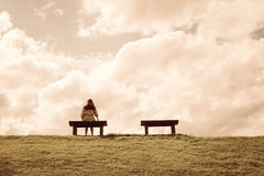 A women sitting alone on a bench waiting for love. A woman sitting alone on a bench waiting for love, alone concept Stock Photo