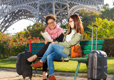 Women sitting on a bench and reading map of Paris Royalty Free Stock Photo