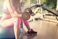 The women sitting on big ball and plays dumbbell in Fitness room and warm light.  stock photo
