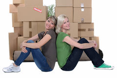 Women sitting by boxes stock photos