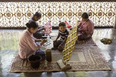 Women sitting on carpets in temple making intricate flower offerings for worshipers Stock Image