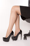 Women is sitting on the chair. Businesswoman wearing high heels black shoes and sitting on the chair Stock Images