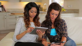 Women sitting on the couch. Both holding a tablet PC stock video
