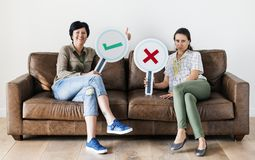 Women sitting on couch holding icons Royalty Free Stock Photography