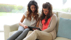 Women sitting on the couch while holding a tablet PC stock video